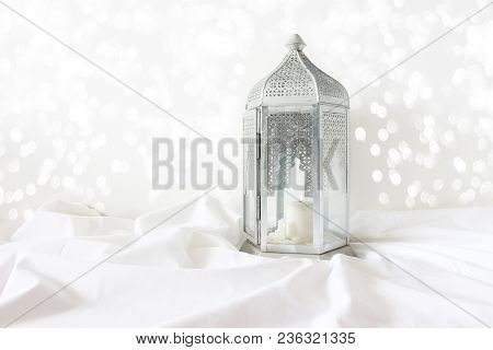 Ornamental Silver Moroccan, Arabic Lantern On White Linen Throw. Burning Candle, Glittering Bokeh Li