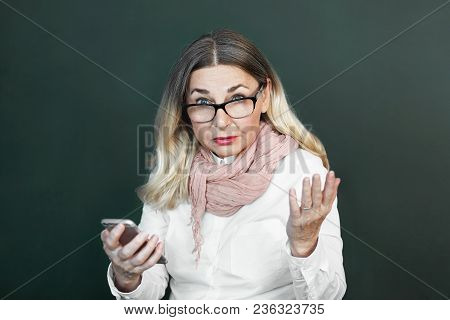 Stressed Indignant Middle Aged Caucasian Female In Stylish Clothes Gesturing In Confusion, Having Pr