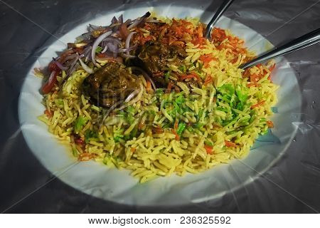 Special Mutton Kacchi Biryani Rice With Chili Onion Lime On A Plate. Traditional Indian Cuisine. Bri