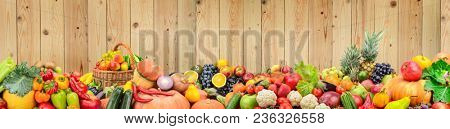 Panoramic photo healthy vegetables and fruits against light wooden wall. Free space for text.