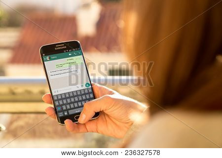 Rosario, Argentina - August 8, 2017: Girl With Smartphone In Her Hands And A Whatsapp Conversation O