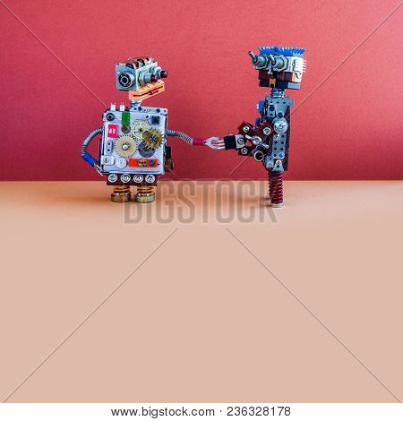 Two Robots Greet Each Other. Handshake Of Cybernetic Mechanical Cyborgs. Creative Design Robotic Toy