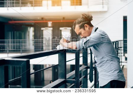 Businessman Standing On Balcony Office Room With Crumpled Paper.