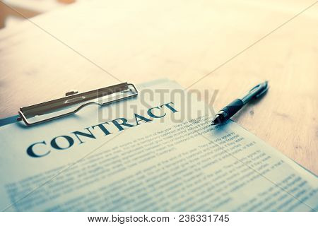 Contract Paper With Pen On Desk.