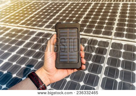 Green Energy, Photovoltaic Solar Cell With Hand. Mobile Power Bank In Hand On The Background Of Larg