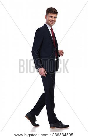 side view of laughing businessman dressed in a navy suit and a red tie walking on white background, full body picture