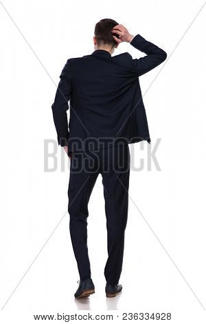 back view of businessman wearing a navy suit, scratching his head and thinking while standing on white background, full body picture