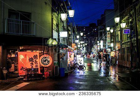 Osaka, Japan - April 14, 2018: Lights Reflect Off A Quiet Street After Heavy Rain Storm