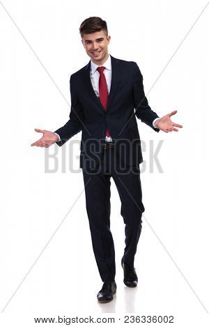 greeting businessman with navy suit and red tie smiling and stepping forward on white background, full body shot