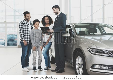 African American Family At Car Dealership. Salesman Is Signing Papers For New Grey Car.