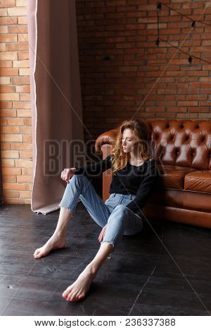 Young Woman In Casual Clothes Sitting On Floor Next To Brown Leather Sofa.