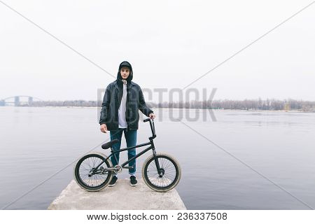 Portrait Of A Bmx Rider Standing With A Bike On The Background Of The River. Walking With Bmx By Bik