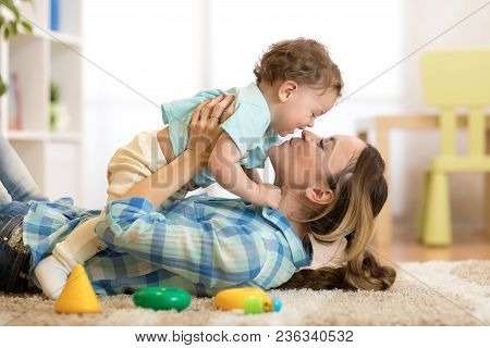 Happy Mother With Her Baby Toddler Having Fun Pastime On The Carpet In Nursery