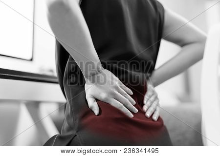 Business Woman With Back Pain An Office. Healthcare And Medical Concept - Black And White Color Imag
