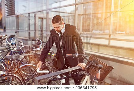 Young business man with headphones puts bicycle on bicycle rack in the city