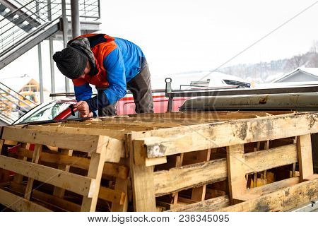 Man Is Loading Wooden Pallets On A Truck In Winter.