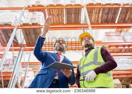 Low Angle Portrait Of Mature Businessman Holding Clipboard Talking To Worker Wearing Hardhat And Ref