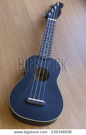 Ululele Guitar Close Up Photo On Wooden Table Surgace