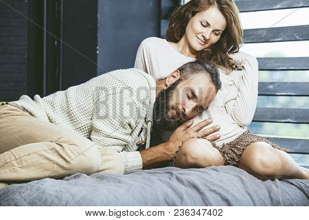 Heterosexual Couple Beautiful Young Man And A Pregnant Woman On Bed In Bedroom At Home