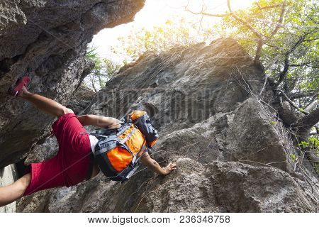 Man With  Backpack Climbing Rock Mountain,or Latin Man Backpack Climbing In Thailand Rock Mountain W