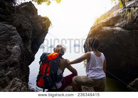 Brother And Brother Are Looking Beach On The Rock Mountain With Background Of Sunset On The Sea.