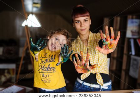 Young Mother And Her Son Playing With Color Paints In Art Studio.