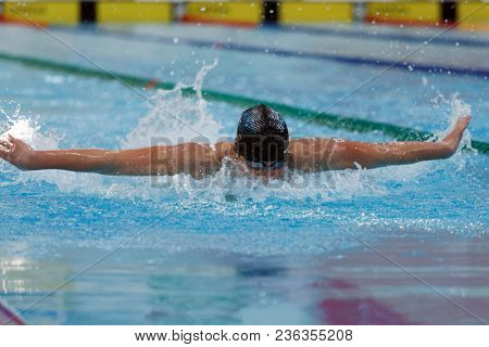 ST. PETERSBURG, RUSSIA - APRIL 11, 2018: Men compete in 100m butterfly swimming during All-Russian Swimming Competitions Merry Dolphin. The competitions was founded in 1965