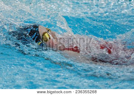 ST. PETERSBURG, RUSSIA - APRIL 11, 2018: Girl competes in 100m backstroke swimming during All-Russian Swimming Competitions Merry Dolphin. The competitions was founded in 1965