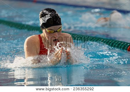 ST. PETERSBURG, RUSSIA - APRIL 11, 2018: Girls compete in 4x50m breaststroke relay swimming during All-Russian Swimming Competitions Merry Dolphin. The competitions was founded in 1965