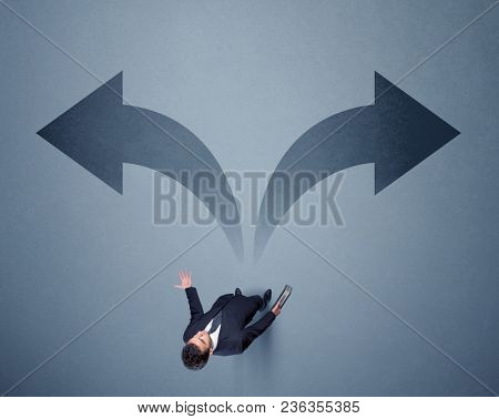 Young smart businessman standing in front of two arrows potinting to different ways contemplating a decision