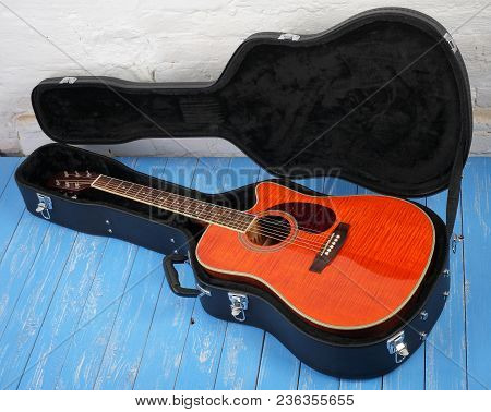 Musical Instrument - Orange Acoustic Guitar In Hard Case On A Blue Wood, And White Brock Wall Backgr