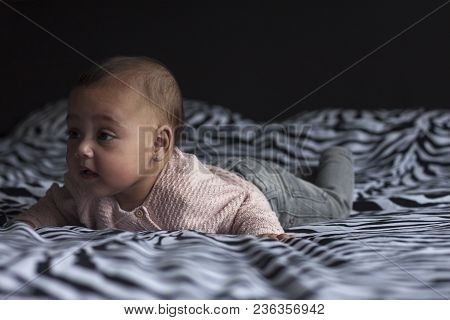Portrait Of A 5 Months Old Adorable Baby Girl Lying On Belly On Parents Bed Looking In The Camera