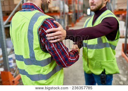 Mid-section Portrait Of Two Warehouse Workers Wearing Reflective Jackets Patting Each Other On Back
