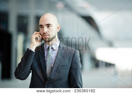 Contemporary businessman in formalwear speaking by mobile phone while traveling in foreign country
