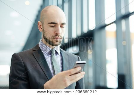 Serious businessman with smartphone reading message while walking along airport lounge