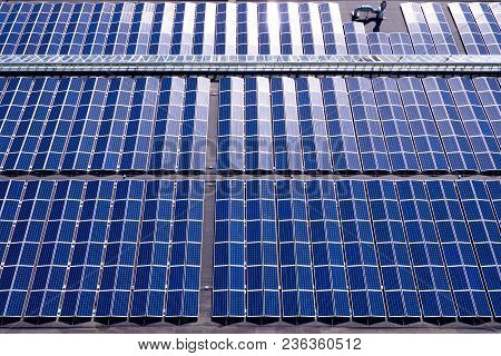 Aerial View Of Blue Solar Panels Installed On Roof. Panels Are Arranged In A East-west Configuration