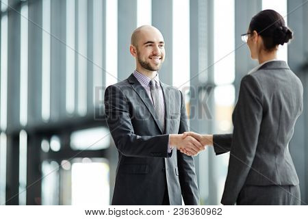 Young successful business partners greeting one another by handshake on arrival in airport lounge