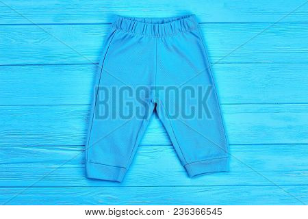 Infant Boy Cotton Pants Isolated. High Quality Cotton Pants For Baby-boy, Blue Wooden Background. Br