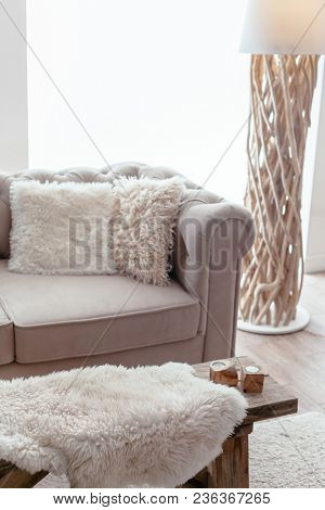 Still life details of nordic living room. Sheep skin rug on rustic bench by the sofa with fur cushions. Cozy winter scene in Scandinavian interior.