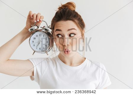 Mystery woman in casual clothes holing alarm clock and looking on it over grey background