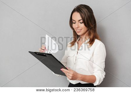Image of an amazing cheerful young business woman standing isolated over grey wall background holding clipboard.