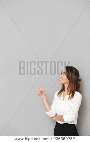 Image of excited cheerful young business woman standing isolated over grey wall background looking aside pointing.