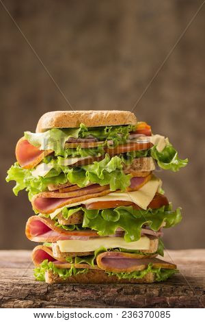 Large Shiny Sandwich With Ham Cheese And Greens On A Wooden Background Looks Very Appetizing