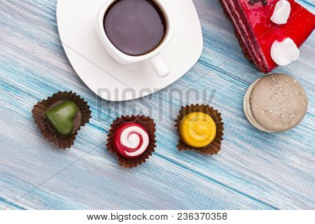 Bright Confectionery And A Cup Of Coffee On A Wooden Background Looks Very Appetizing