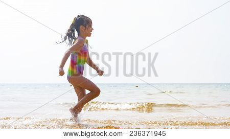 Happy Child Running And Jumping In The Waves During Summer Vacation On Exotic Tropical Beach. Holida