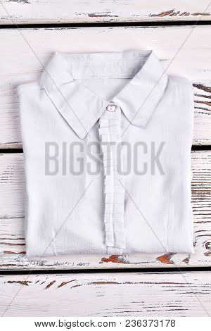 New Folded White Cotton Girls Shirt. School Girls White Long Sleeve Cotton Blouse On Old Wooden Back
