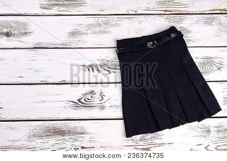 Black Belted Skirt For School Wear. Pleated Black Uniform Skirt On Old Wooden Background.