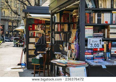 Milan, Italy - April 14, 2018: An Older Man With A Cowboy Hat Sells Books On The Street