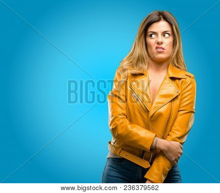 Beautiful young woman irritated and angry expressing negative emotion, annoyed with someone, blue background