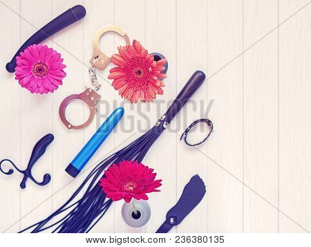 Various Sex Toys And Gerbera Flowers In Vases Are On A Light Wooden Background. Image For Sex Shop A